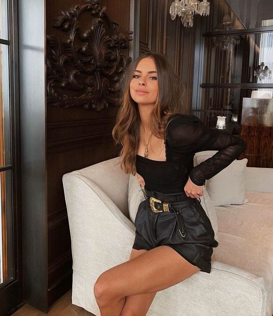 a black sheer top with puff sleeves and a square neckline, black leather shorts with porckets for a chic and sexy look