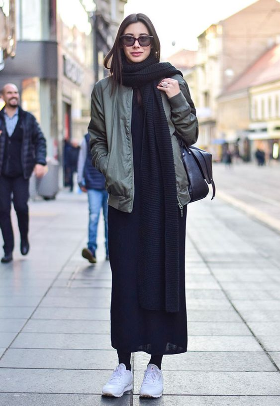 a black sweater dress, a black scarf, a green bomber jacket, white trainers and a black bag