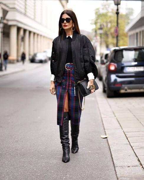 a black sweater over a white shirt, a plai midi pencil skirt, black boots, a black bomber jacket and a black bag