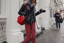 a black sweater, red plaid pants, black boots, a black leather jacket, a gey scarf and a red backpack for a comfy look