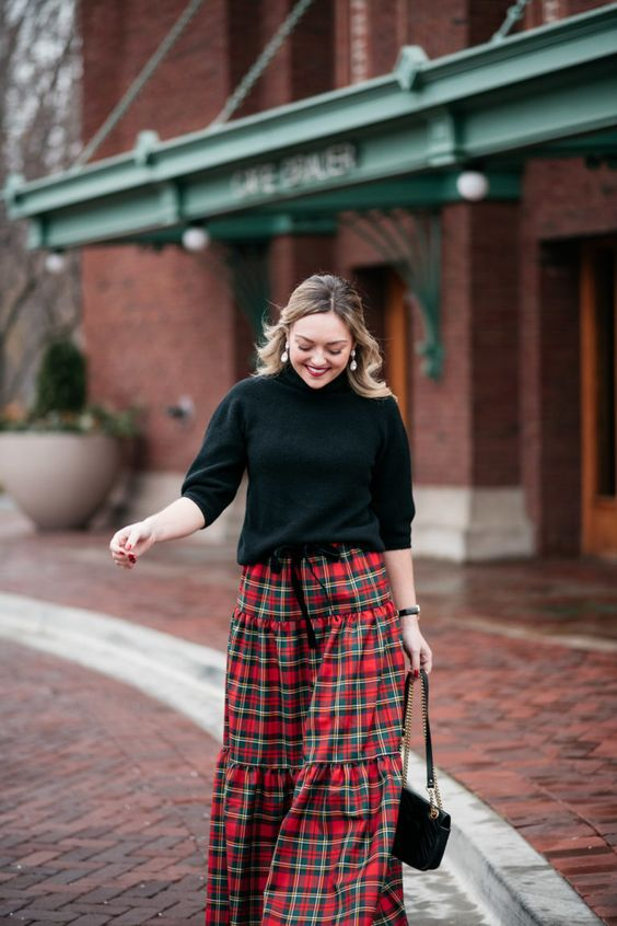 a black sweater with a turtleneck and short sleeves, a plaid A-line maxi skirt and a black bag