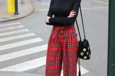 a black turtleneck, red plaid wideleg palazzo pants, a black bag with shiny polka dots