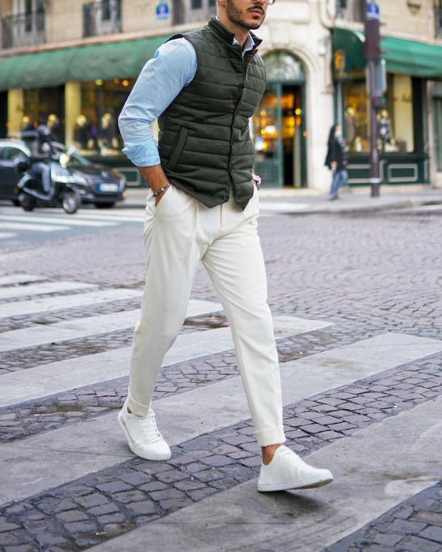 a blue shirt, a green puffer waistcoat, creamy pants and sneakers for a bold and chic look