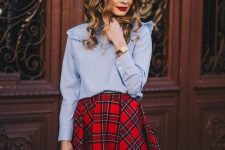 a blue shirt with ruffle detailing and long sleeves, a red plaid mini skirt, a red bag and black thigh boots