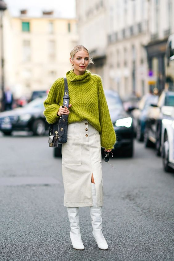a bold and catchy winter outfit with a neon green sweater, a white midi skirt with pockets, white knee high boots and a black bag