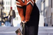 a bold geometric print sweater with a high neckline, a black pencil midi, white ankle booties and a black bag for a chic look