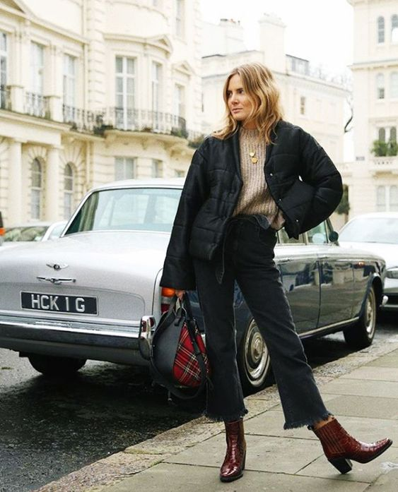 a bold winter look with a tan high neck sweater, black flare jeans, burgundy cowboy boots, a black puffer jacket is wow