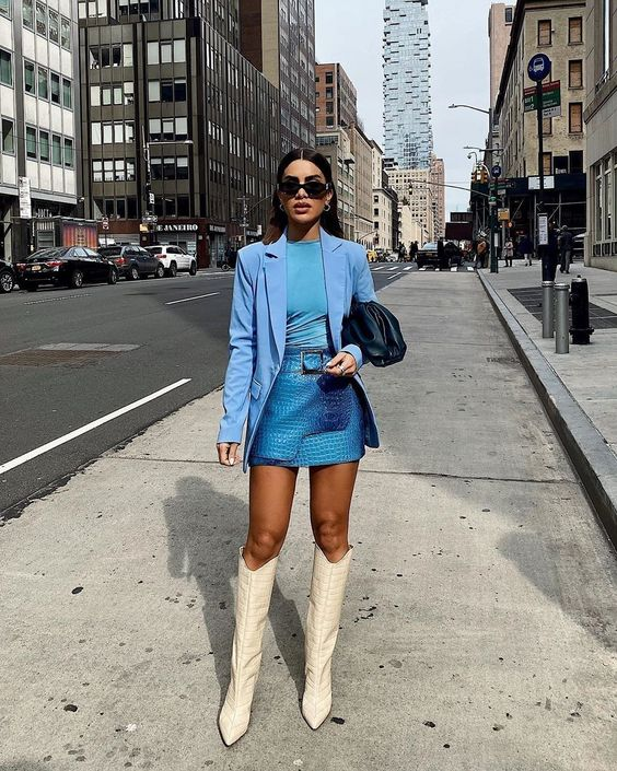 a bright outfit with a bold blue top, blazer, electric blue snakeskin mini skirt, white boots