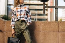 a bright printed sweater, olive green pants, white ankle boots and a black bag for a bold work look
