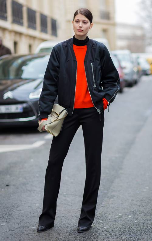 a bright red sweater, black pants, black heels, a black bomber jacket and a neutral bag