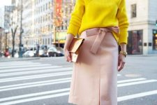 a bright yellow turtleneck sweater, a blush skirt with a bow, rose gold shoes and a shiny clutch for a non-traditional look