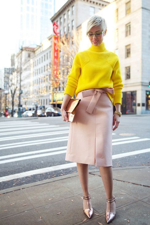 a bright yellow turtleneck sweater, a blush skirt with a bow, rose gold shoes and a shiny clutch for a non traditional look