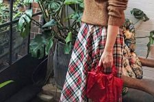 a brown sweater, a bold plaid pleated midi, vintage brown shoes and a red bag for pulling off a vintage holiday look