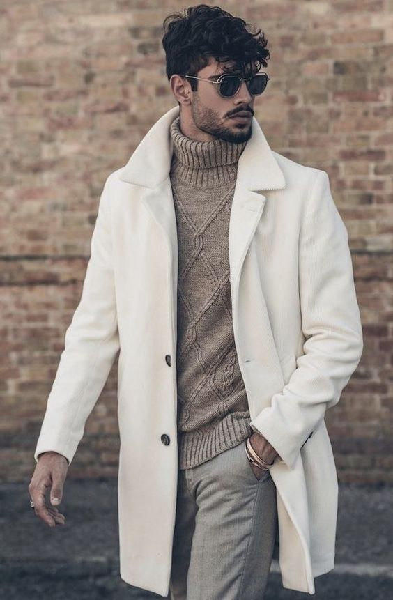 a casual look with grey pants, a tan cable knit sweater is made elegant with a refined white coat