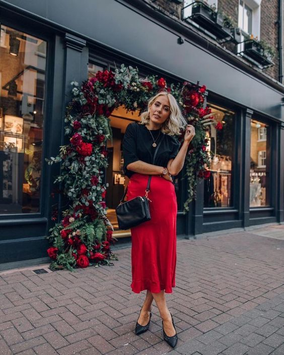 a chic look with a black top with a high neckline, a red slip midi skirt, a black bag and shoes for the holidays