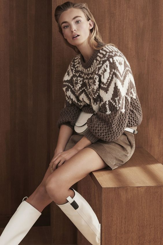a chic oversized printed sweater in brown and white, a corduroy mini, a white waist bag and white boots