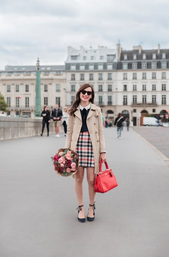 a chic preppy look with color - a white shirt, a black jumper, a bright plaid mini, black lace up shoes, a red bag and a tan trench