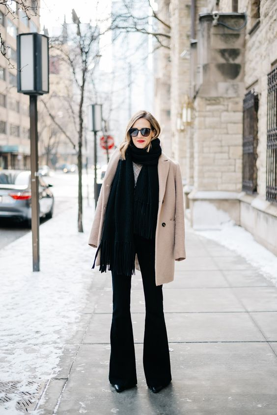 a chic winter look with a grey sweater, black flare jeans, boots, a black scarf and a short tan coat