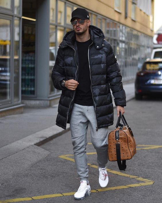 a comfy winter look with a black jumper, grey joggers, white trainers, a black printed puffer jacket, a cap and a large bag