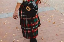 a cozy white sweater, a plaid pleated midi skirt, black boots and a black bag for a cozy look
