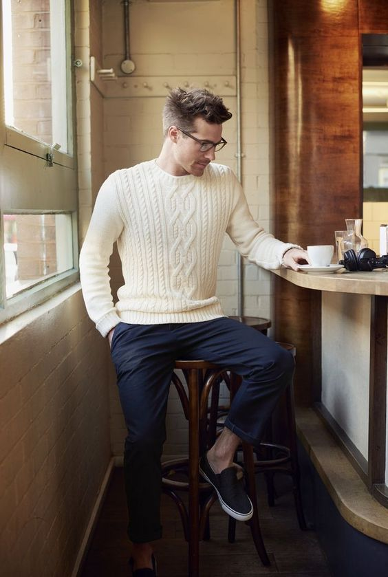 a cozy winter outfit wih navy trousers, a white cable knit sweater and black slipons for feeling warm