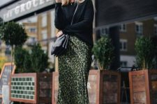 a creative look with a black sweater, a green leopard print midi skirt, black combat boots and a black bag