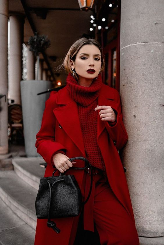 a dramatic total red look with a sweater, pants, a coat and a black bag plus a dark lip is wow