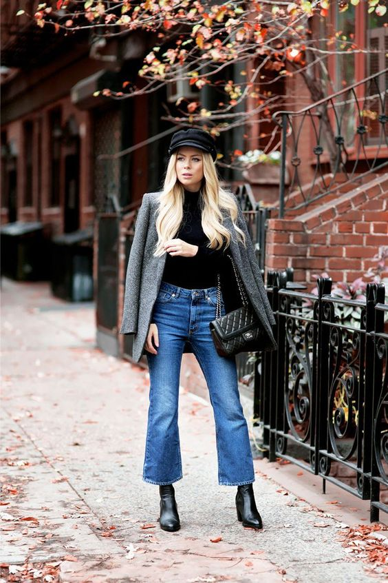 a fall or winter outfit with a black tutleneck, blue flare jeans, black boots, a black bag, a grey blazer and a cap