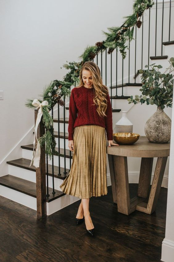 a gold pleated midi skirt, a burgundy cable knit sweater, black shoes for a holiday look in traditional colors