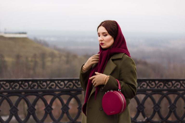 a green coat, a purple woolen headscarf and a fuchsia round bag for a stylish winter look with a colorful touch