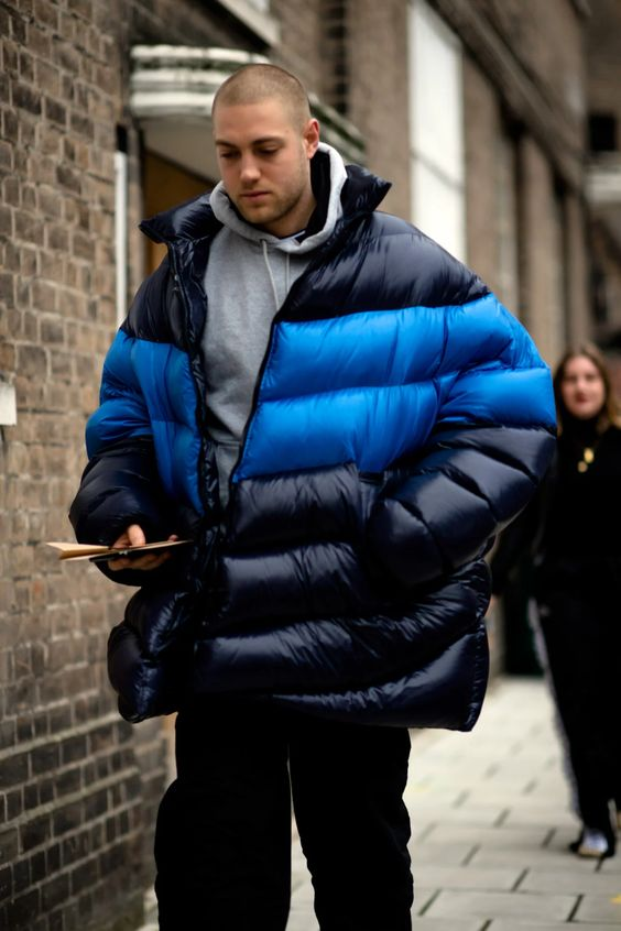 a grey hoodie, black jeans, a bold navy and blue blanket puffer jacket for a statement