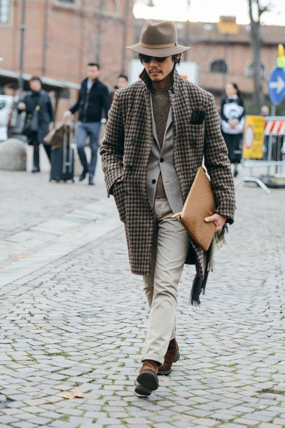 a grey jumper, a dove grey pantsuit, a printed coat, brown shoes, a grey hat and a clutch