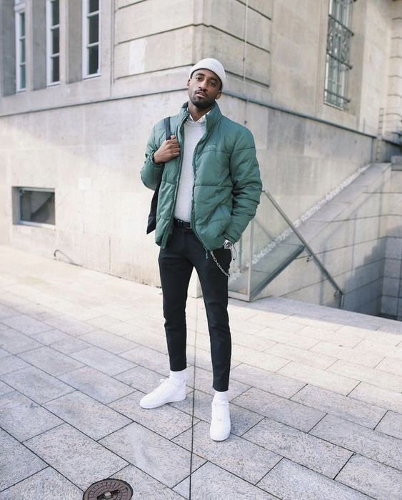 a grey jumper over a white shirt, black jeans, white trainers, a green puffer jacket and a beanie