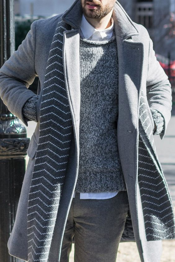 a layered winte rlook in grey with a white shirt,a grey sweater, grey trousers, a grey coat and a printed scarf