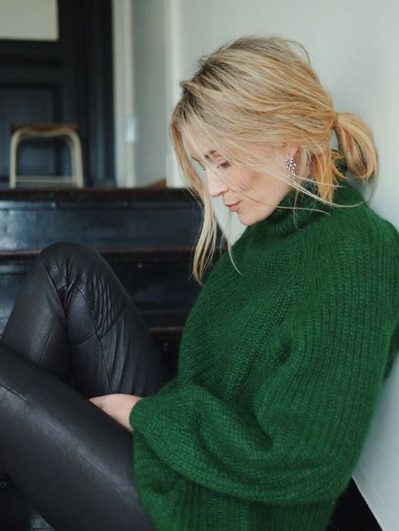 a messy yet chic holiday look with a green turtleneck sweater, black leather pants and statement earrings