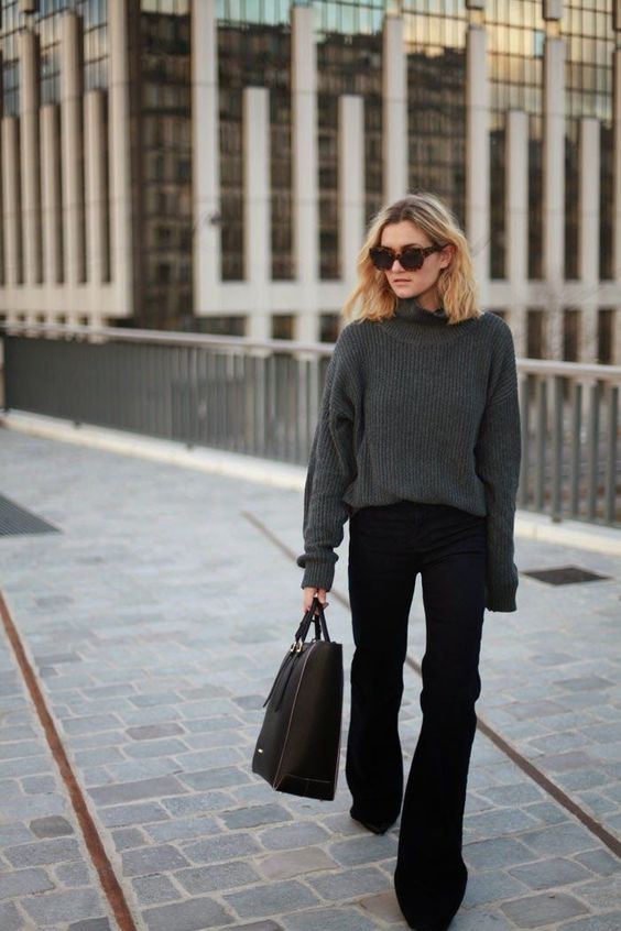 a minimalist look with a graphite grey sweater, black flare jeans, black boots, a black tote
