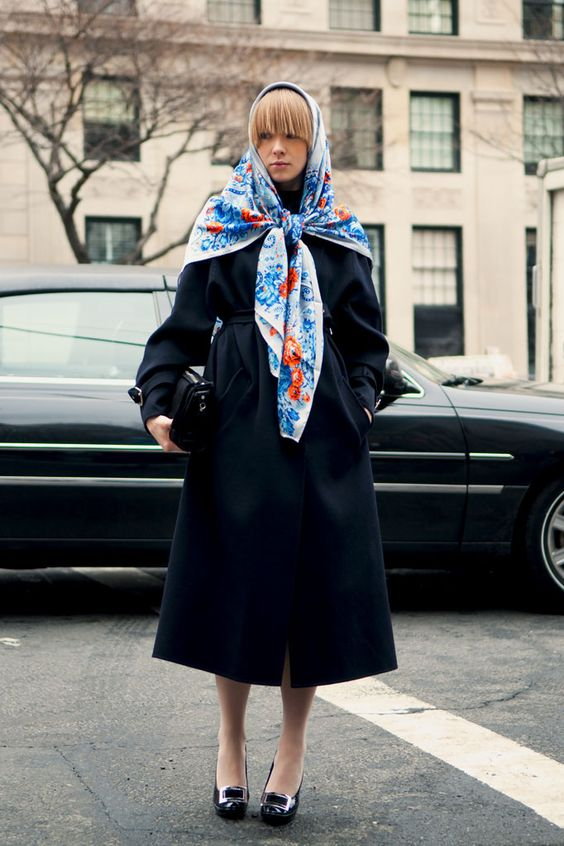 a navy midi coat with a sash and a bright blue and red printed headscarf for a unique retro look