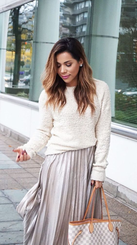 a neutral sweater with long sleeves, a grey pleated midi skirt and statement earrings for holidays