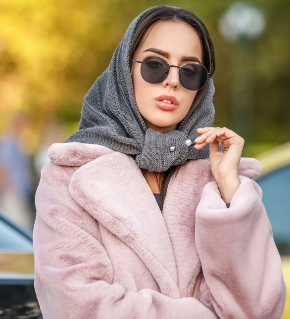 a pink faux fur coat plus a grey woolen headscarf accented with a pearl pin for a veyr chic and girlish look