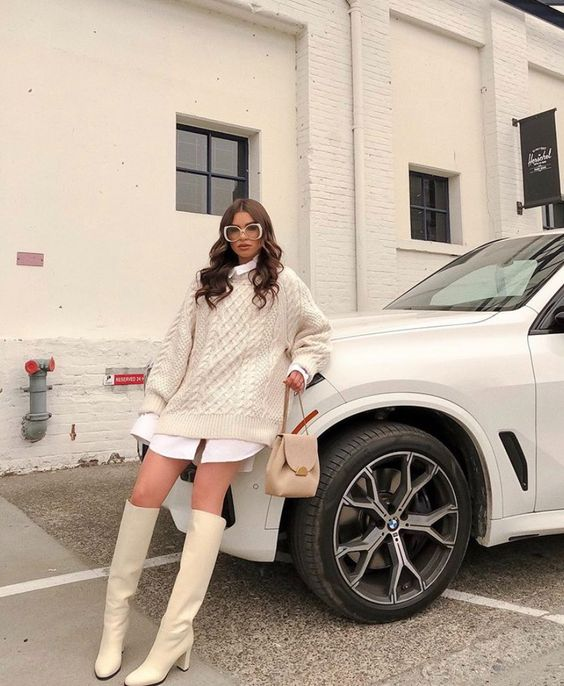 a preppy neutral look with a white oversized shirt, an ivory oversized sweater over it, ivory knee high boots and a tan bag