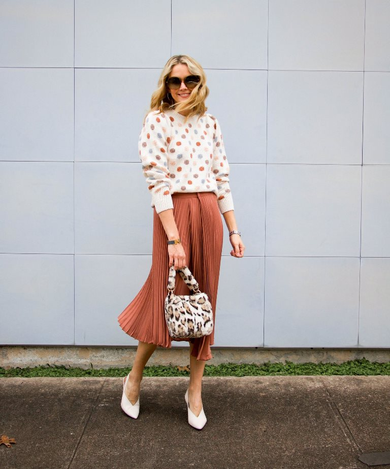 a pretty polka dot sweater, a terracotta pleated midi and a fluffy faux fur bag for a girlish feel