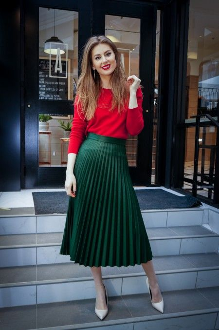 a red long sleeve top,, a green pleated midi skirt, white shoes for a stylish holiday work look