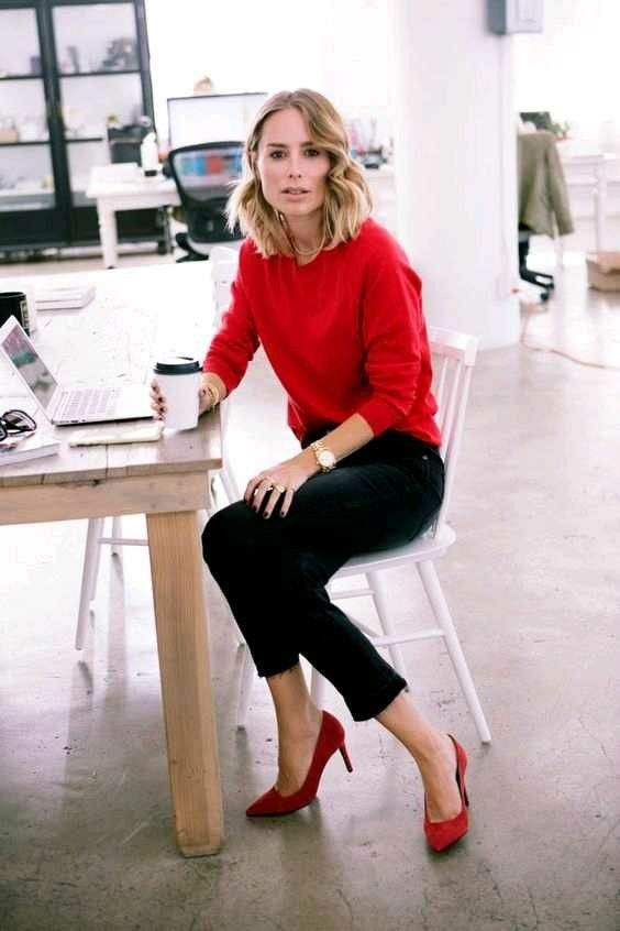a red sweatshirt, black jeans with a raw hem and red shoes make up an easy and chic look