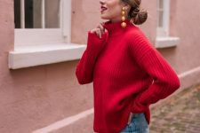 a red turtleneck sweater, blue skinnies and statement earrings for a chic and bold holiday look