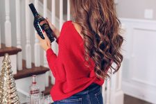 a red wrap sweater with an open back and blue skinnies are all you need for a gorgeous holiday look