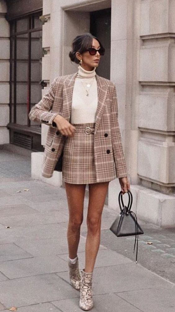 a refined work outfit of a neutral plaid mini skirt suit, a creamy turtleneck, snakeskin print boots and a black triangle bag