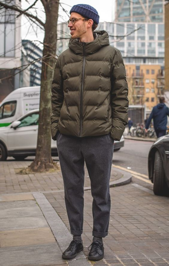a relaxed winter outfit with a grene short puffer jacket, grey pants, black sneakers and a navy beanie