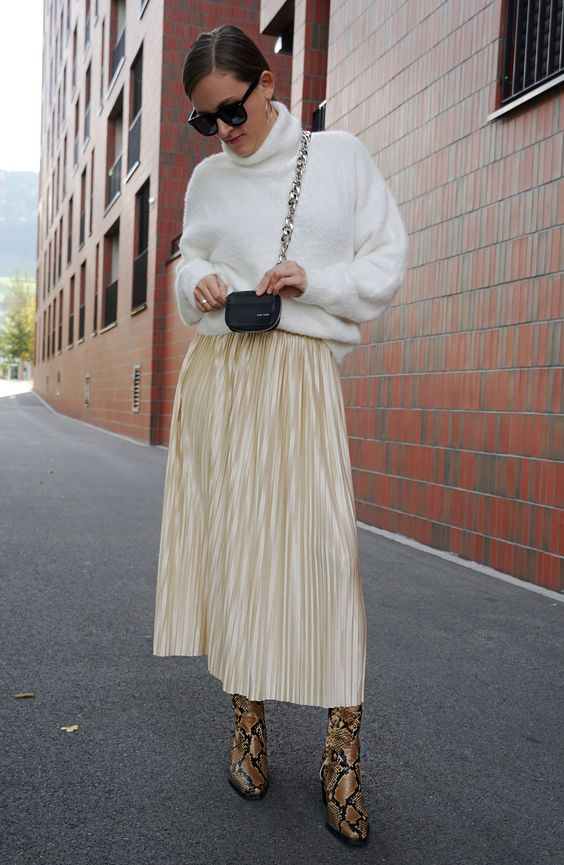 a simple and chic outfit with a white sweater, a gold pleated midi, snakeskin boots and a tiny black bag