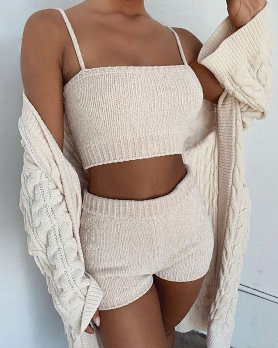 a simple and cozy two piece knit set with a crop top and shorts and a cable knit cardigan added