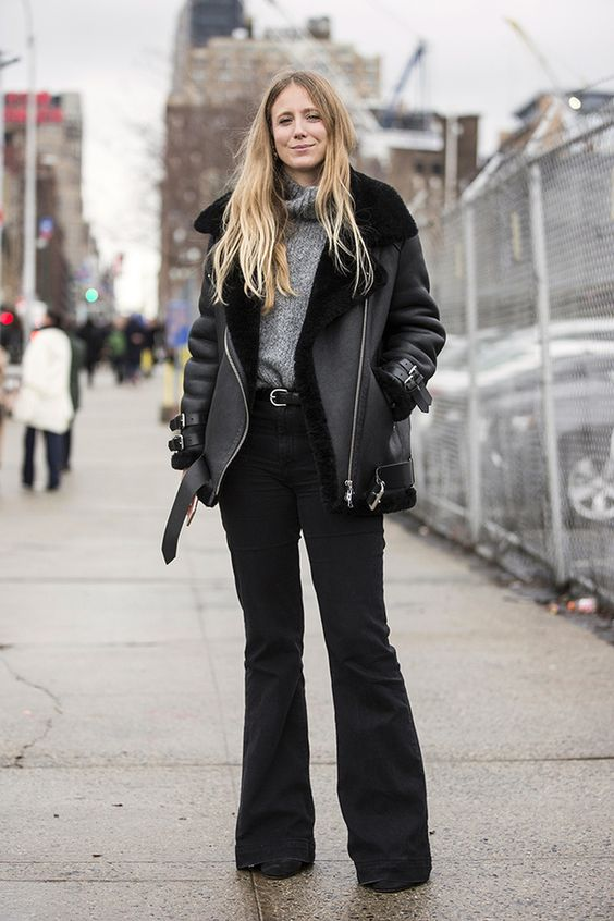 a simple outfit with a grey turtleneck sweater, black flare jeans, black boots, an oversized shearling coat